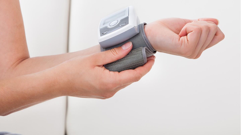 Eine Frau bei der Blutdruckmessung am Handgelenk.