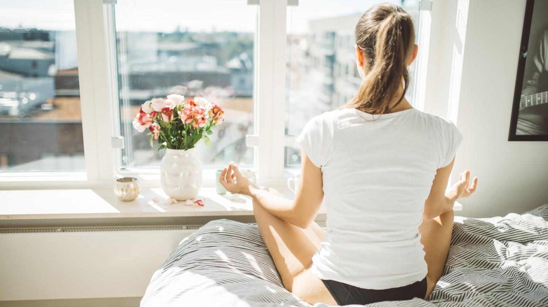 Resilienz aufbauen: Junge Frau in weißem T-Shirt sitzt auf dem Bett und macht Yoga-Entspannungsübung mit Blick aus dem Fenster.